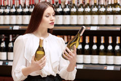Woman holds a wine bottle in the store Royalty Free Stock Images