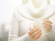 Woman holds a winter cup close up. Woman hands with elegant french manicure nails design holding cozy knitted mug. Stock Photo