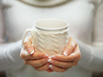 Woman holds a winter cup close up. Woman hands with elegant french manicure nails design holding a cozy knitted mug. Stock Photography