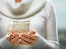 Woman holds a winter cup close up. Woman hands with elegant french manicure nails design holding a cozy knitted mug. Stock Photo