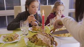 Woman cuts fried chicken at the festive table. Woman holds a wooden fork and knife and cuts a delicious fried chicken. Two little daughters and father observes stock footage