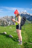 Woman on holiday in the mountains on an excursion check the emai Stock Photography