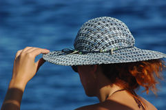 Woman on holidays, holding hear hat and looking out to sea. Caucasian, unrecognizable redhead woman holding with left hand her blue hat and looking out to sea Royalty Free Stock Photography