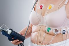 Woman with holter monitor device for daily monitoring of electrocardiogram and blood pressure. On gray background royalty free stock photography