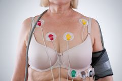 Woman with holter monitor device for daily monitoring of electrocardiogram and blood pressure. On gray background stock images