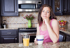 Woman at home. Pretty woman having breakfast in a kitchen Stock Photography