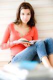 Woman At Home. A young woman sitting on the floor with a book stock photography