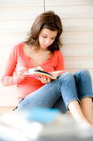 Woman At Home. A young woman sitting on the floor with a book stock image