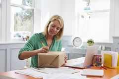 Woman At Home Addressing Package For Mailing Royalty Free Stock Photos