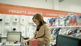 A woman in a home appliance shop pays for the goods. stock footage