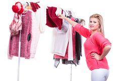Woman in home closet choosing clothing, indecision. Young woman indecision in wardrobe home closet, teen blonde girl choosing her warm fashion outfit on clothing royalty free stock photos