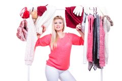 Woman in home closet choosing clothing, indecision. Young woman indecision in wardrobe home closet, teen blonde girl choosing her warm fashion outfit on clothing stock photo