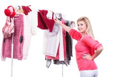 Woman in home closet choosing clothing, indecision. Young woman indecision in wardrobe home closet, teen blonde girl choosing her warm fashion outfit on clothing stock photography