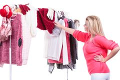 Woman in home closet choosing clothing, indecision. Young woman indecision in wardrobe home closet, teen blonde girl choosing her warm fashion outfit on clothing royalty free stock photography