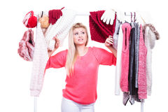 Woman in home closet choosing clothing, indecision. Young woman indecision in wardrobe home closet, teen blonde girl choosing her warm fashion outfit on clothing royalty free stock images