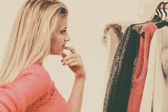 Woman in home closet choosing clothing, indecision. Young woman indecision in wardrobe, teen blonde girl choosing her warm winter fashion outfit in walk in royalty free stock photos