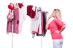 Woman in home closet choosing clothing, indecision. Young woman indecision in wardrobe, teen blonde girl choosing her warm winter fashion outfit in walk in stock photography