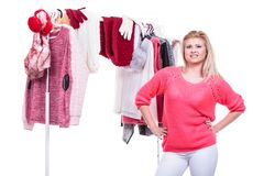 Woman in home closet choosing clothing, indecision. Young woman indecision in wardrobe home closet, teen blonde girl choosing her warm fashion outfit on clothing royalty free stock image