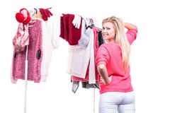 Woman in home closet choosing clothing, indecision. Young woman indecision in wardrobe home closet, teen blonde girl choosing her warm fashion outfit on clothing stock images