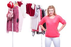 Woman in home closet choosing clothing, indecision. Young woman indecision in wardrobe home closet, teen blonde girl choosing her warm fashion outfit on clothing stock photos