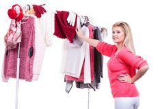 Woman in home closet choosing clothing, indecision. Young woman indecision in wardrobe home closet, teen blonde girl choosing her warm fashion outfit on clothing royalty free stock photo