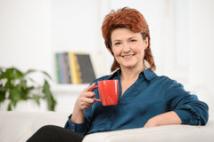 Woman at home with cup of tea Stock Photography