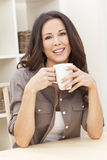 Woman At Home Drinking Tea or Coffee. Beautiful, smiling, young brunette woman at home at a table drinking a mug of tea or coffee royalty free stock image