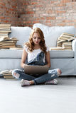 Woman at home. Education. Woman sitting on a sofa, surrounded with heap of books stock image