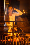 Woman at home fireplace making fire with bellows. Stock Image