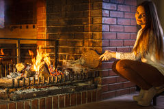 Woman at home fireplace making fire with bellows. Stock Photos