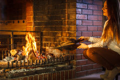 Woman at home fireplace making fire with bellows. Royalty Free Stock Images