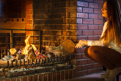 Woman at home fireplace making fire with bellows. Royalty Free Stock Photo