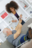 Woman home help assisting elder man with treatment Royalty Free Stock Images