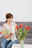 Woman at home holding flowers Royalty Free Stock Photos