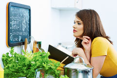 Woman in home kitchen cooking bio diet. Menu Royalty Free Stock Photo