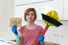 Woman at home kitchen in gloves with cleaning broom and mop asking for help Stock Photography