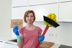 Woman at home kitchen in gloves with cleaning broom and mop asking for help royalty free stock image
