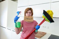 Woman at home kitchen in gloves with cleaning broom and mop asking for help Royalty Free Stock Photography