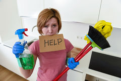 Woman at home kitchen in gloves with cleaning broom and mop asking for help Stock Photo