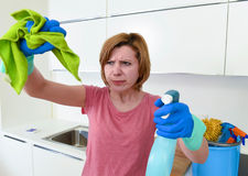 Woman at home kitchen in gloves holding cleaning scourer and detergent spray bottle rubbing with cloth. Attractive service woman or housewife at home kitchen in Stock Images