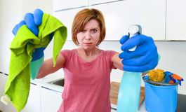 Woman at home kitchen in gloves holding cleaning scourer and detergent spray bottle rubbing with cloth Stock Images