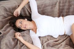 Woman at home laying on sofa Stock Images