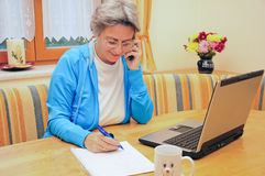 Woman in home office. Mature woman working in her home office Royalty Free Stock Images