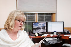 Woman home office. Mature woman reading and on the phone in a home office royalty free stock photo