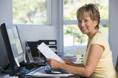 Woman in home office with computer and paperwork Stock Images