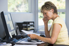 Woman in home office with computer and paperwork Stock Photo