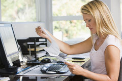 Woman in home office with computer and paperwork Stock Photography