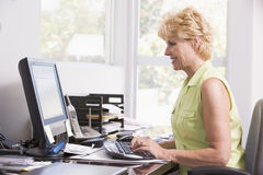 Woman in home office at computer smiling Stock Photos