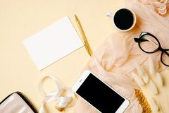 Woman home office desk with white paper card, mobile phone, coffee cup, glasses, silk scarf and accessories on beige background. Flat lay beauty blogger royalty free stock photo