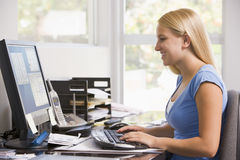 Woman in home office using computer Royalty Free Stock Image